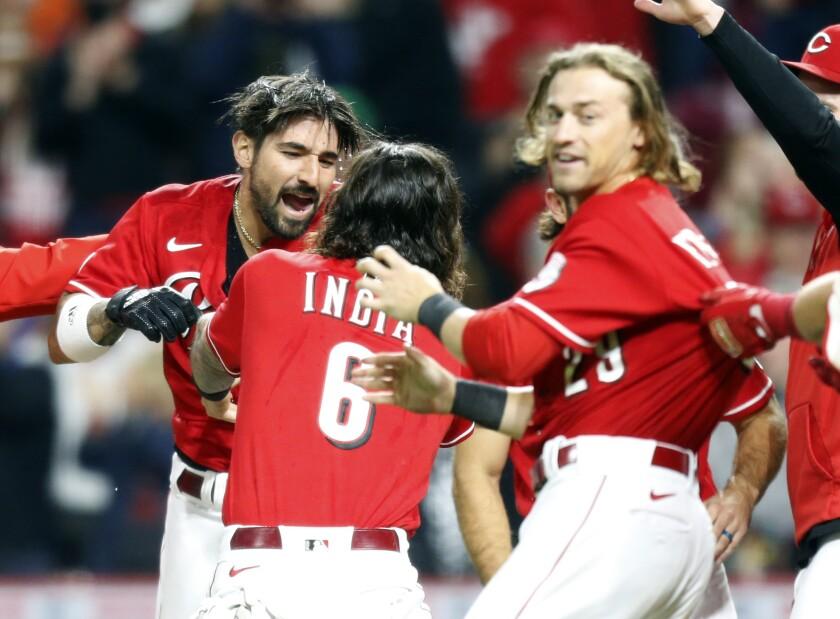 Nick Castellanos (izquierda), de los Rojos de Cincinnati, festeja con sus compañeros Jonathan India y TJ Friedl, luego de batear un jonrón ante los Nacionales de Washington, el sábado 25 de septiembre de 2021 (AP Foto/Paul Vernon)