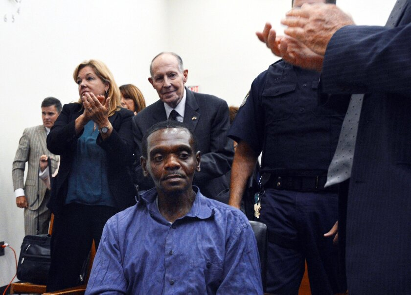 Henry McCollum sits stunned as applause rings out after a North Carolina judge declared McCollum and his half-brother, Leon Brown, were innocent of a rape-murder for which they spent more than 30 years in prison. The half-brothers are still awaiting a pardon before they can receive compensation.