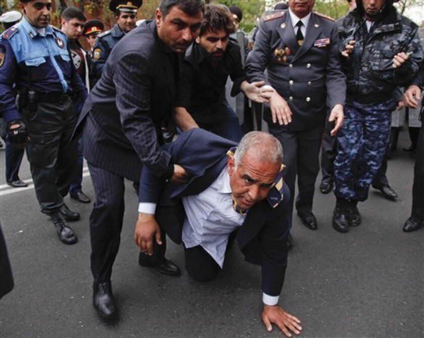 Armenian election runner-up Raffi Hovanessian is helped up after he fell during clashes between his supporters and police in Yerevan, Armenia, Tuesday, April 9, 2013. Armenian President Serge Sarkisian has been sworn in for another five-year term to lead the small former Soviet republic amid street protests by his opponents. Thousands of Hovanessian's supporters gathered in the capital to protest the inauguration. (AP Photo/Tigran Mehrabyan, PanARMENIAN)
