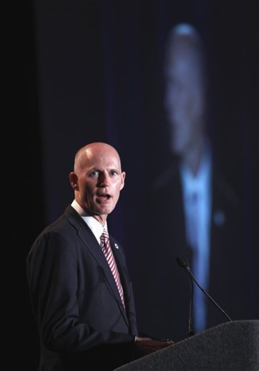FILE - In this May 18, 2011 file photo, Florida Gov. Rick Scott speaks in Fort Lauderdale, Fla. In office just six months, Scott has kept his campaign promises and then some: cutting corporate taxes, reducing the size of government, drug testing welfare recipients, making government workers pay into their pensions, and privatizing Medicaid. (AP Photo/Wilfredo Lee, File)