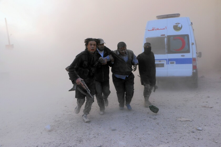 Al Nusra Front fighters help a wounded man after a barrel bomb attack, reportedly by government forces, in the northern Syrian city of Aleppo on Nov. 6, 2014.