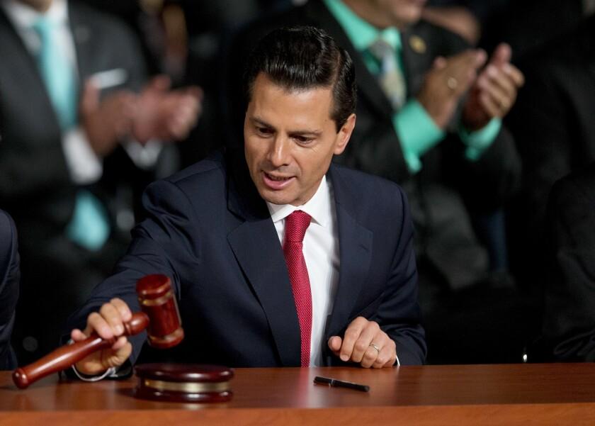 El presidente mexicano, Enrique Peña Nieto, revisa un martillo de madera justo después de que se utilizó para inaugurar el nuevo sistema de justicia penal de México, tras reformas que han tomado años en desarrollarse, al filo del primer minuto del sábado 18 de junio de 2016, en la Ciudad de México. (AP Foto/Rebecca Blackwell)