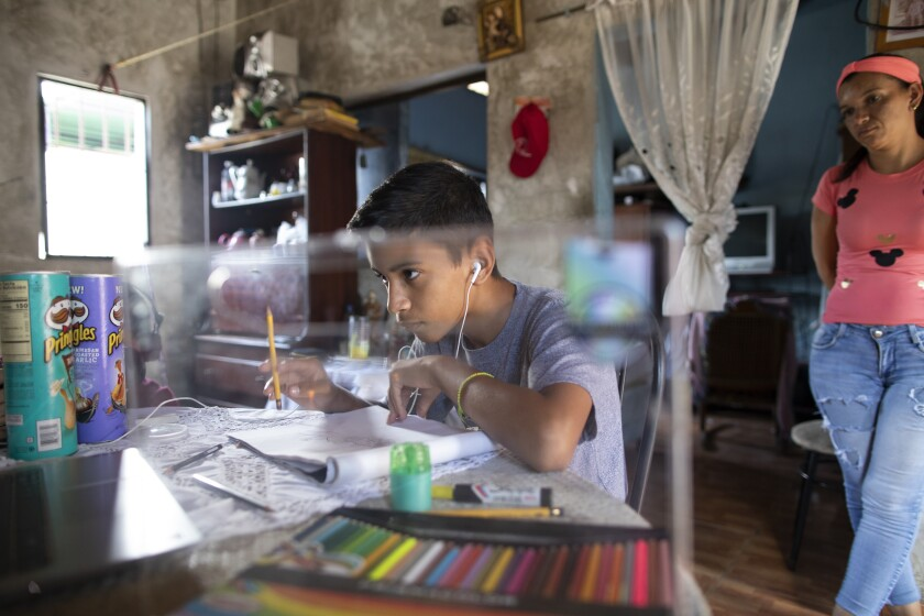 Samuel Andres Mendoza looks at a picture of a Pokemon on his computer before drawing it, at his home in Barquisimeto, Venezuela, Tuesday, March 2, 2021. The 14-year-old has been selling his drawings on his Twitter account to help the family get by. (AP Photo/Ariana Cubillos)