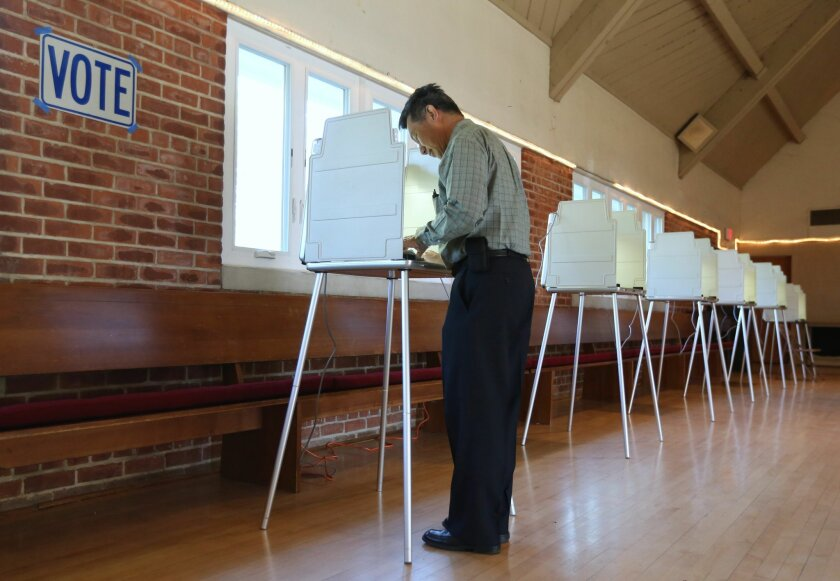 Mike Lee marks his ballot while voting in the California Primary, in Sacramento,Calif., Tuesday, June 3, 2014.  With no divisive ballot initiatives or high-profile races a low voter turnout is expected.(AP Photo/Rich Pedroncelli)