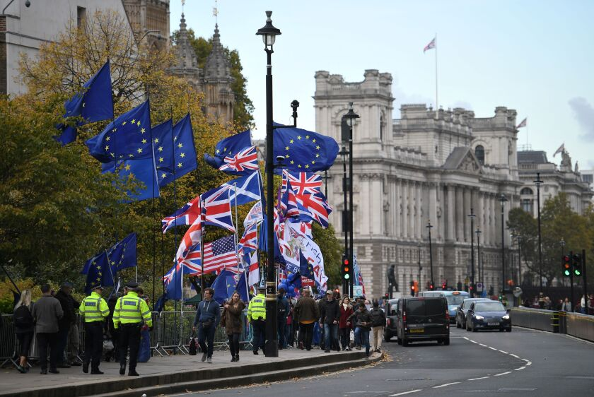 Protesters carry European Union and Union Jack flags on the sidewalk near the Houses of Parliament in central London on Oct. 29, 2019.