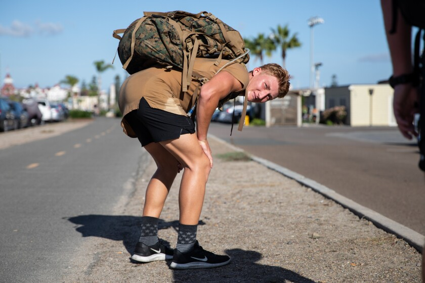 Air Force ROTC cadet Hayden Butchko rests after participating in the 13 mile ruck walk