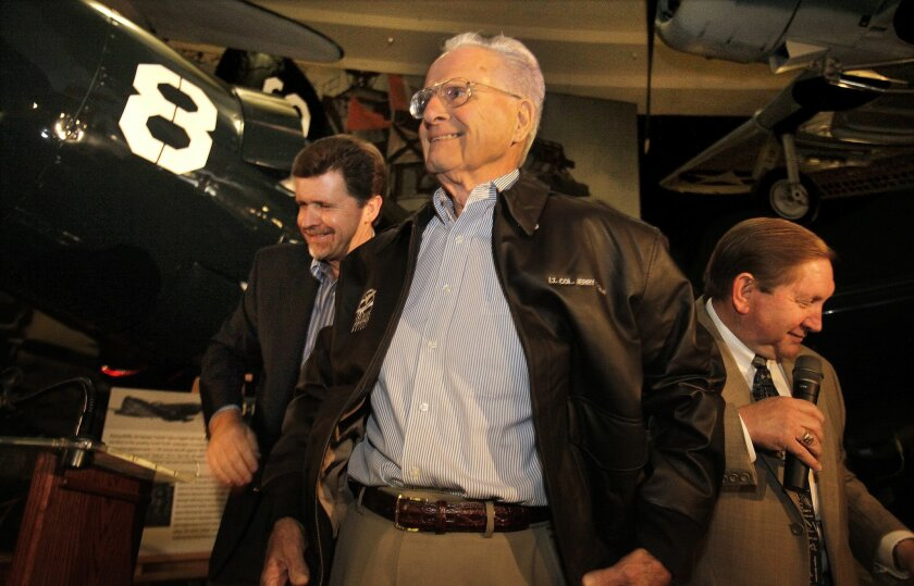 Jerry Coleman, Padres' Hall of Fame broadcaster, wears a leather flight jacket presented to him Oct. 27 at the San Diego Air and Space Museum in Balboa Park. Mark Larson, left, chairman of the board, and James Kidrick, president and CEO of the museum, honored Coleman during an unveiling of a AU-1