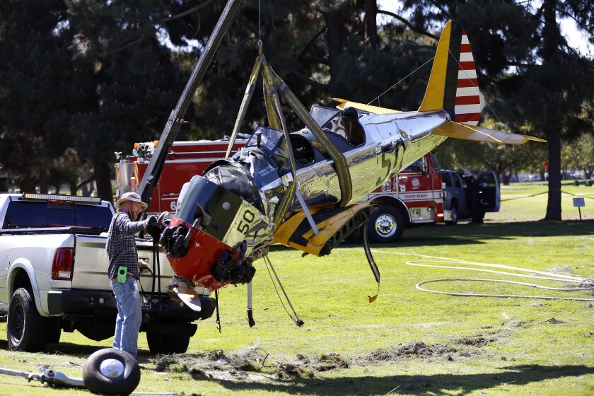 Workers move the vintage plane that crashed on the Penmar golf course not far from Santa Monica Municipal Airport.
