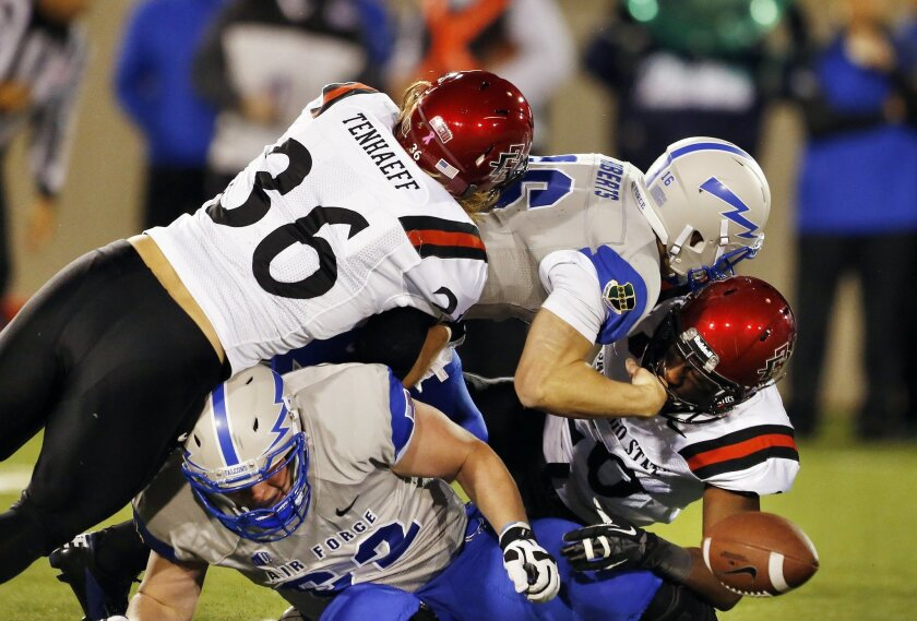 Air Force Academy quarterback Karson Roberts, top right, fumbles as he is tackled on a run by San Diego State linebacker Nick Tenhaeff, and defensive back Nat Berhe.