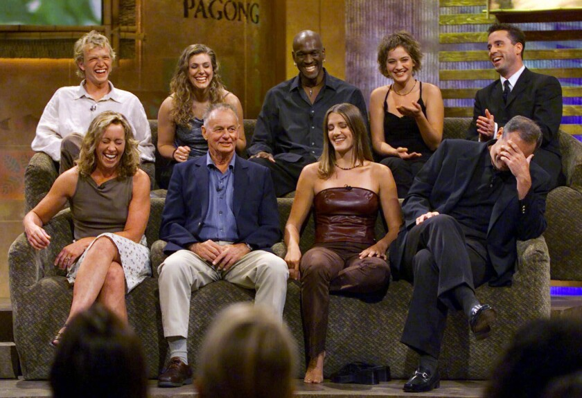 """FILE - In this Aug. 23, 2000, file photo, a group of """"Survivor"""" contestants, break into laughter during a live town hall meeting at CBS Studios in Hollywood in Los Angeles. Survivors are, from left, bottom row, Susan Hawk, Rudy Boesch, Kelly Wiglesworth and Richard Hatch, covering his face, top row, Greg Buis, Jenna Lewis, Gervase Peterson, Colleen Haskell and Sean Kenniff. Boesch, a retired tough-as-nails Navy SEAL and fan favorite on the inaugural season of """"Survivor,"""" died Friday, Nov. 1, 2019, after a long battle with Alzheimer's disease. He was 91. (AP Photo/Kevork Djansezian, File)"""