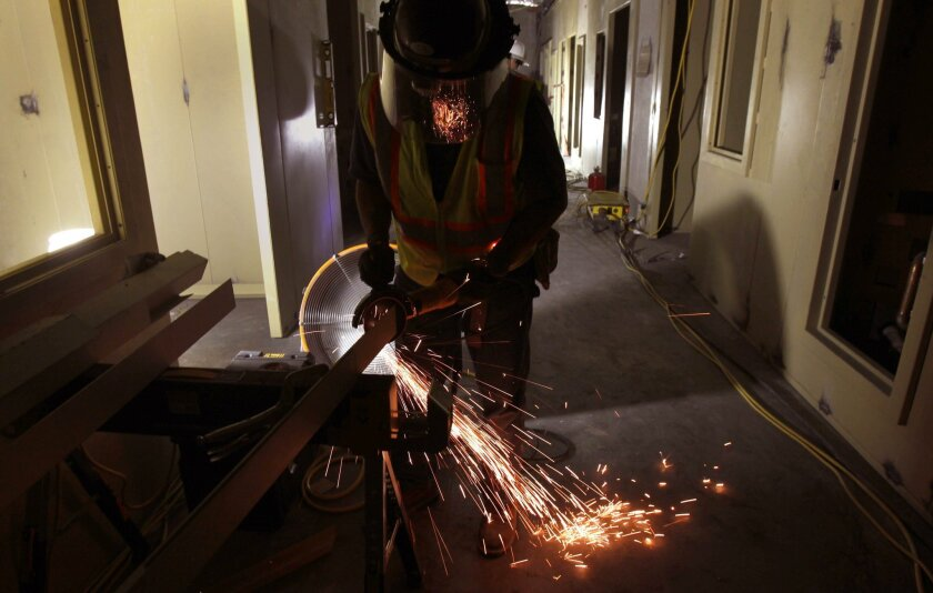 Jose Chavez Vazquez works a grinder on fabricating metal parts of one holding area in the new courthouse