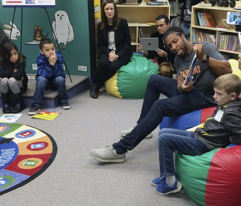 Denver Broncos safety David Bruton Jr., right, reads to students at an elementary school in Aurora, Colo., early on Wednesday, Feb. 17, 2016. Bruton is one of several Broncos defenders set to become a free agent but wishes the defense that helped win Super Bowl 50 less than two weeks ago could rema