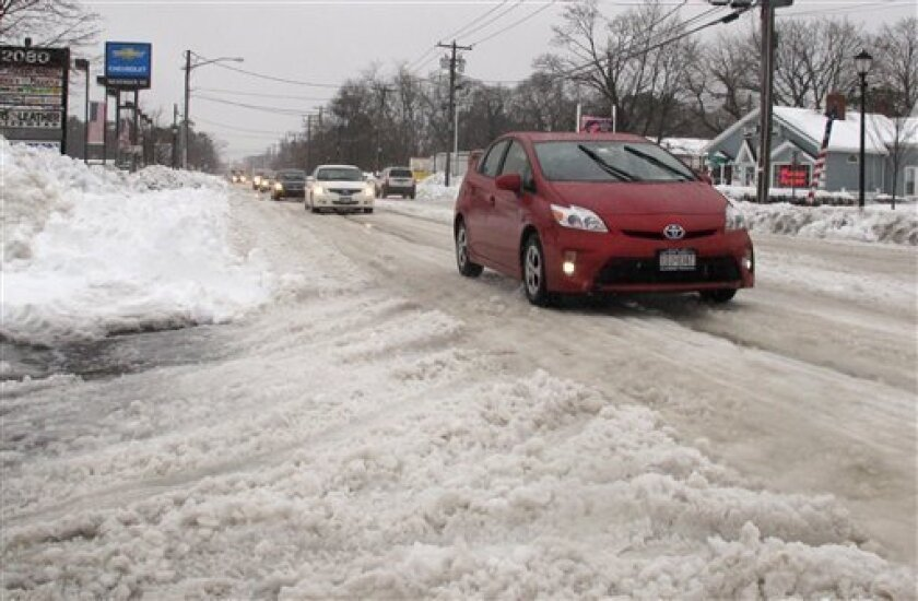 Vehicles try to maneuver across snow and ice-covered state Route 112 in Medford, N.Y., Monday, Feb. 11, 2013. While major highways on eastern Long Island were beginning to recover from a weekend blizzard, many local roads remained covered in snow and ice two days after the storm. (AP Photo/Frank El