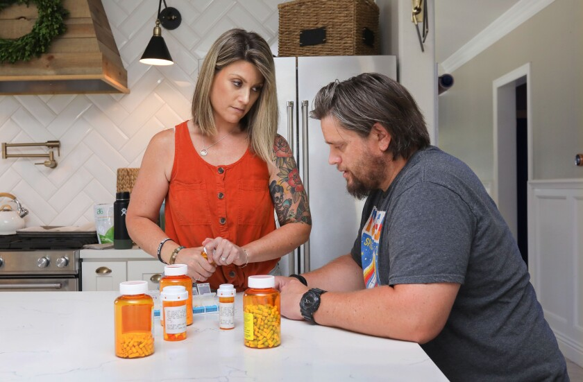 Nikki Stephens assists her husband John as they organize the many medications he needs for the week in their Murrieta home.