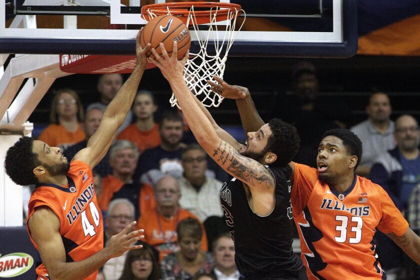 Chicago State forward Jordan Madrid-Andrews, center, goes to the basket against Illinois guard Alex Austin, left, and Illinois forward Mike Thorne Jr. (33) during the first half of an NCAA college basketball game at the Prairie Capital Convention Center, Monday, Nov. 23, 2015, in Springfield, Ill. (AP Photo/Seth Perlman)