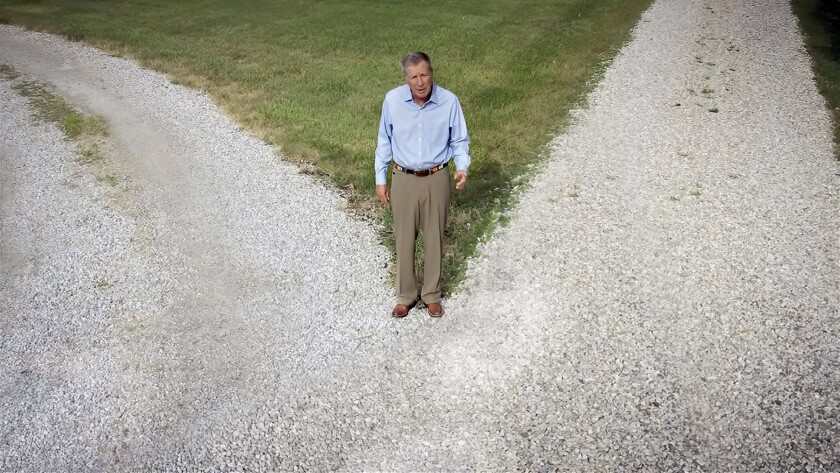 Republican former Ohio Gov. John Kasich stands at a gravel crossroads in a Democratic National Convention video