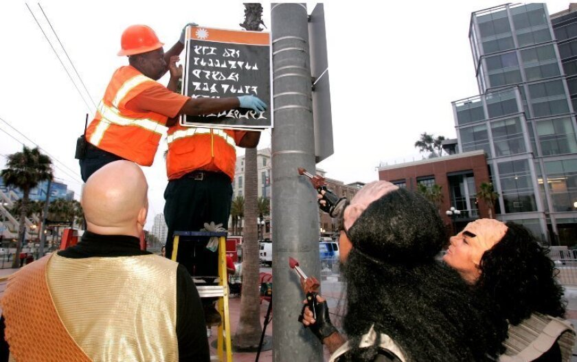 The Klingons showed up punctually at the Gaslamp Trolley Station Tuesday before dawn and by 6:15 a.m. had easily vanquished a handful of TV morning news people as transit workers dutifully climbed up and down a ladder replacing an English direction sign with Klingon version for the cameras.
