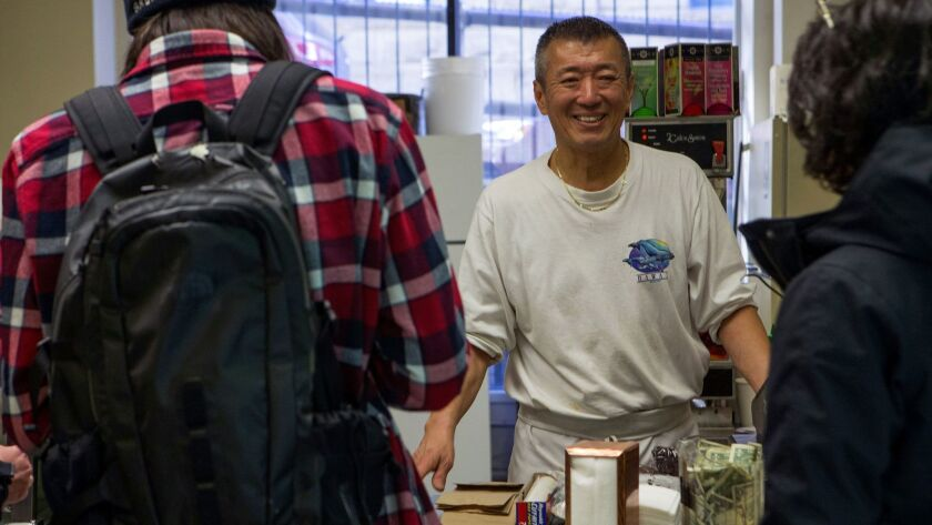Jason Wang, owner, of Bakeman's in downtown Seattle talks to customers Wednesday, December 6, 2017.