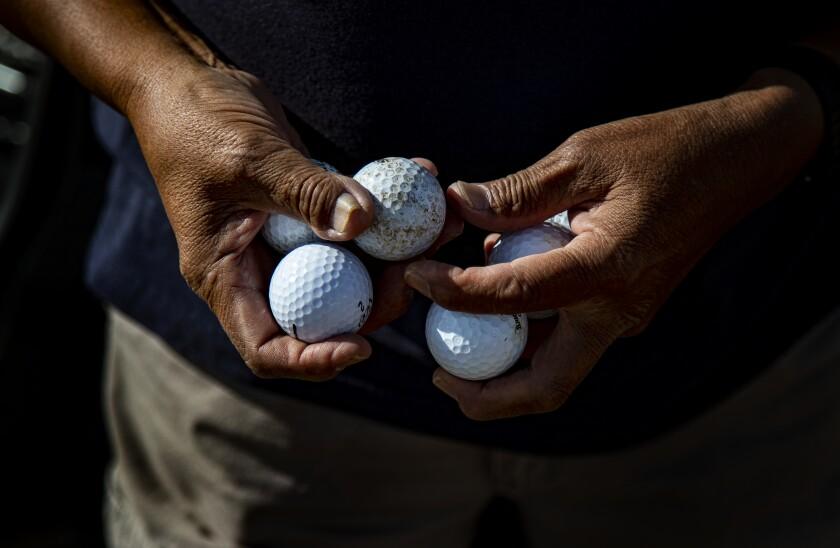 Man holds golf balls.