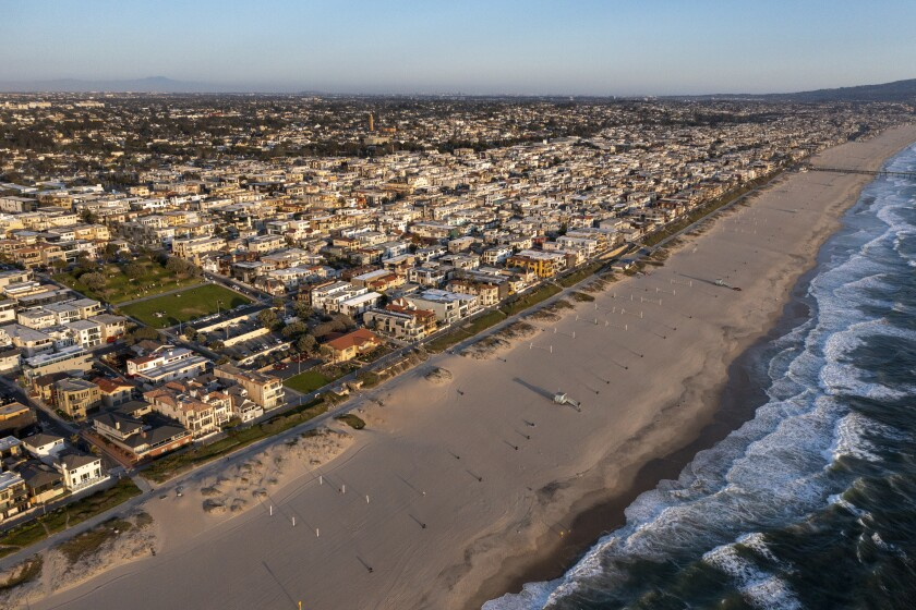 An aerial photo of a sandy beach bordered densely by homes.