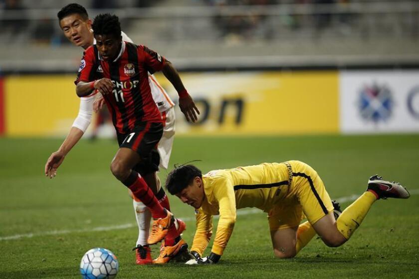 El brasileño Carlos Adriano (i), del South FC Seoul, lucha por el balón con el portero del Shandong Luneng Wang Dalei (d) durante un partido. EFE/Archivo