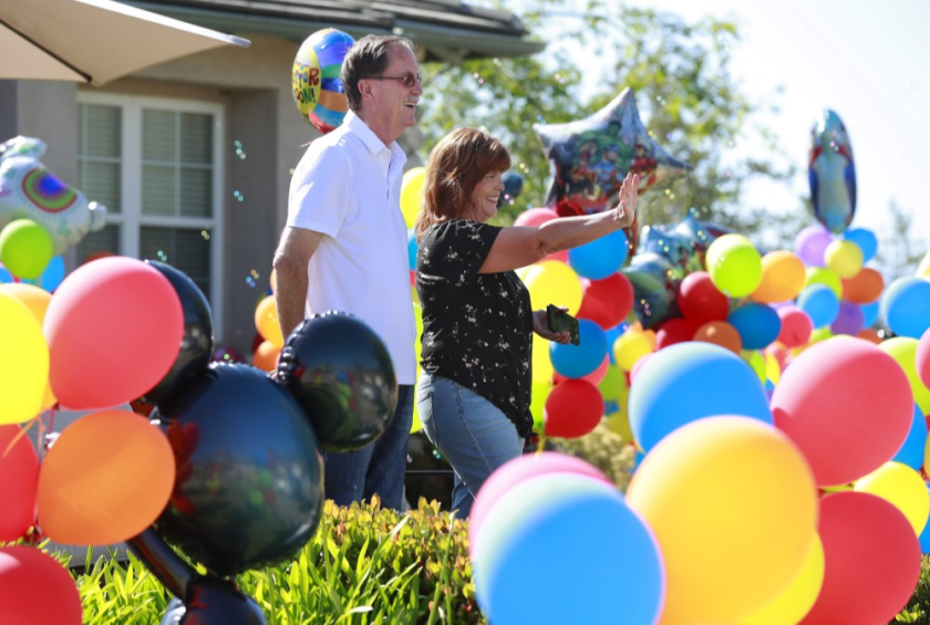 "Walt Ekard, along with his wife Pam, react to well wishers during a drive-by ""get well soon"" event at his Alpine home on May 24. Ekard says treatment is going well after recently being diagnosed with pancreatic cancer."