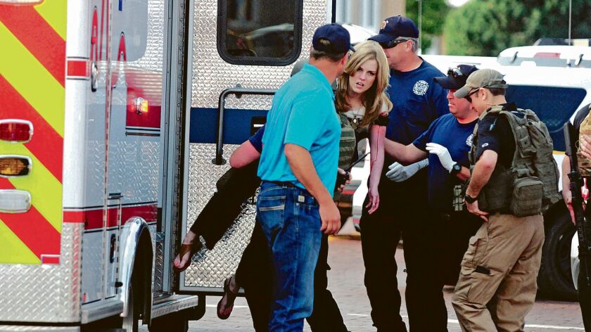 An injured woman is carried to an ambulance in Clovis, N.M., Monday, Aug. 28, 2017, as authorities r