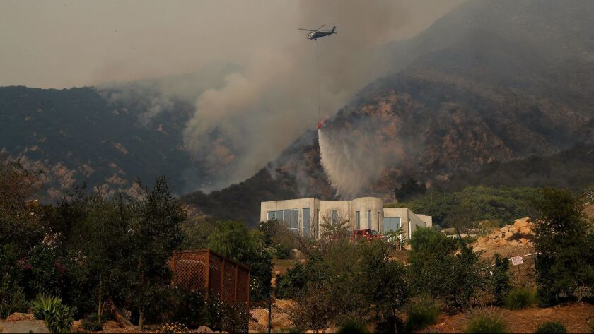 A chopper dumps water on brush above a home on Toro Canyon Road in Montecito as the Thomas fire burns closer.