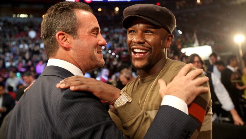 Retired boxing champion Floyd Mayweather Jr. is greeted by Top Rank President Todd duBoef near ringside for the Pacquiao-Vargas fight on Saturday night in Las Vegas.
