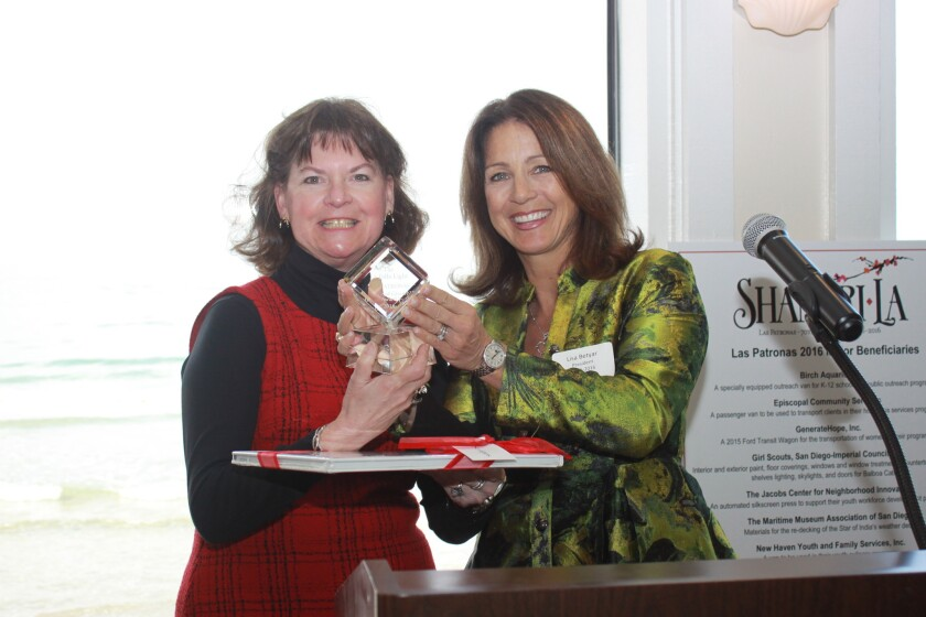 La Jolla Light executive editor Susan DeMaggio accepts the Spirit of Giving Award from Lisa Betyar.