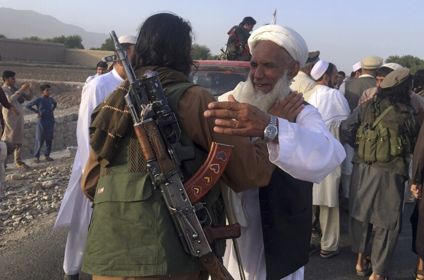 FILE - In this June 16, 2018 file photo, Taliban fighters gather with residents to celebrate a three-day cease fire marking the Islamic holiday of Eid al-Fitr, in Nangarhar province, east of Kabul, Afghanistan. Many Afghans view Saturday's expected signing of a U.S.-Taliban peace deal with a heavy dose of well-earned skepticism. They've spent decades living in a country at war -- some their whole lives — and wonder if they can ever reach a state of peace. (AP Photo/Rahmat Gul, File)