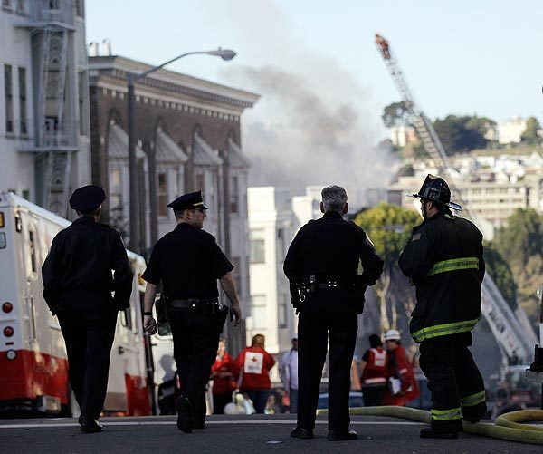 Firefighters and police officers keep watch over an apartment fire in San Francisco's Western Addition on Thursday.