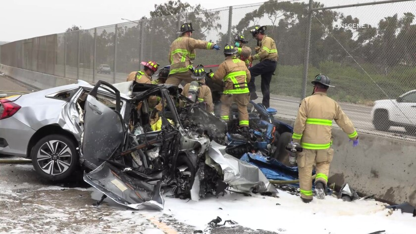 Firefighters work the scene where three people were killed in a wrong-way crash June 4 on Interstate 5 in San Ysidro.