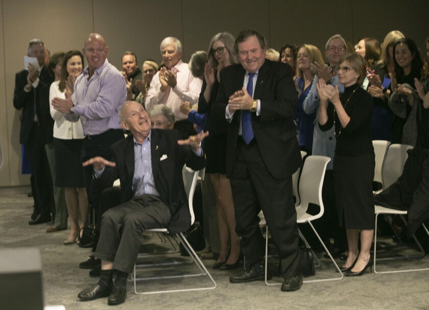 Ernest Rady, seated, urges guests to sit down as they gave him a standing ovation after it was announced Thursday that he and his wife Evelyn had given a $200 million matching gift to Rady Children's Hospital.