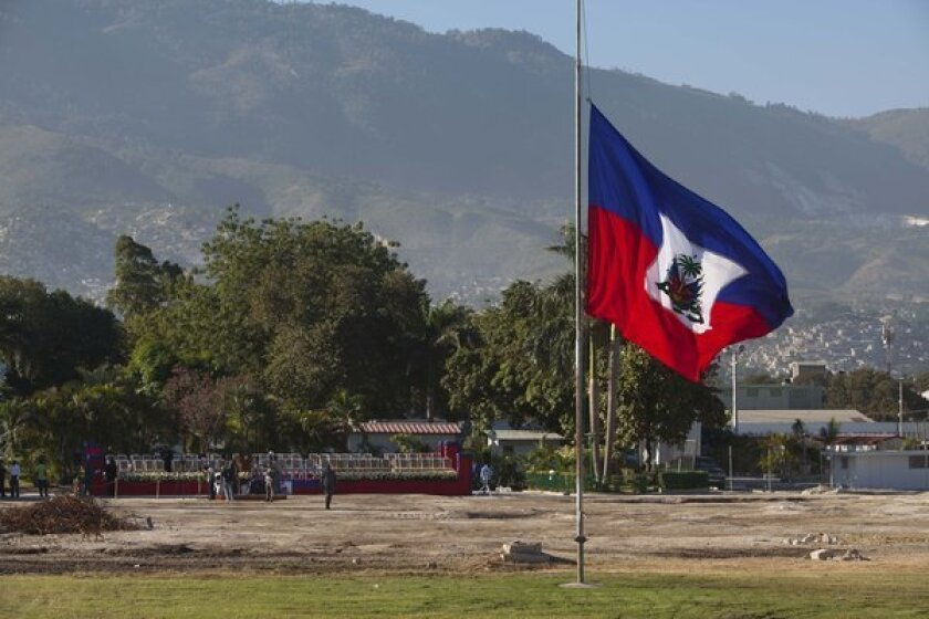 A Haitian national flag flies at half staff on the front lawn of the former National Palace, marking the third anniversary of a devastating earthquake.