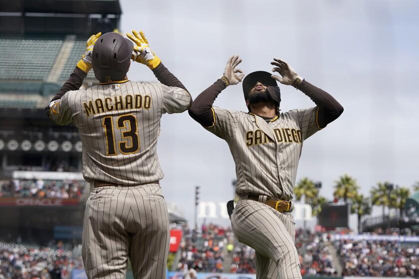 El dominicano Fernando Tatis Jr., de los Padres de San Diego, festeja con su compatriota Manny Machado