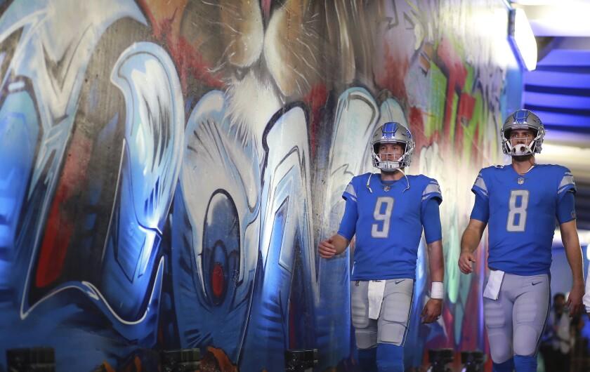 Two Detroit Lions quarterbacks, in uniform, walk past a stadium tunnel mural.