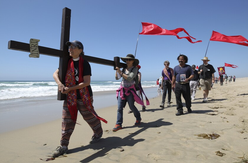 """Jane Gould, left, the rector at St. Luke's Episcopal Church in Long Beach, and Elizabeth Hutchinson, a member of St. Luke's, take their turn carrying a cross as they lead a procession of people participating in the """"Called to the Wall"""" even Saturday. The Los Angeles and San Diego Episcopalian dioceses recognized the Stations of the Cross on the journey."""