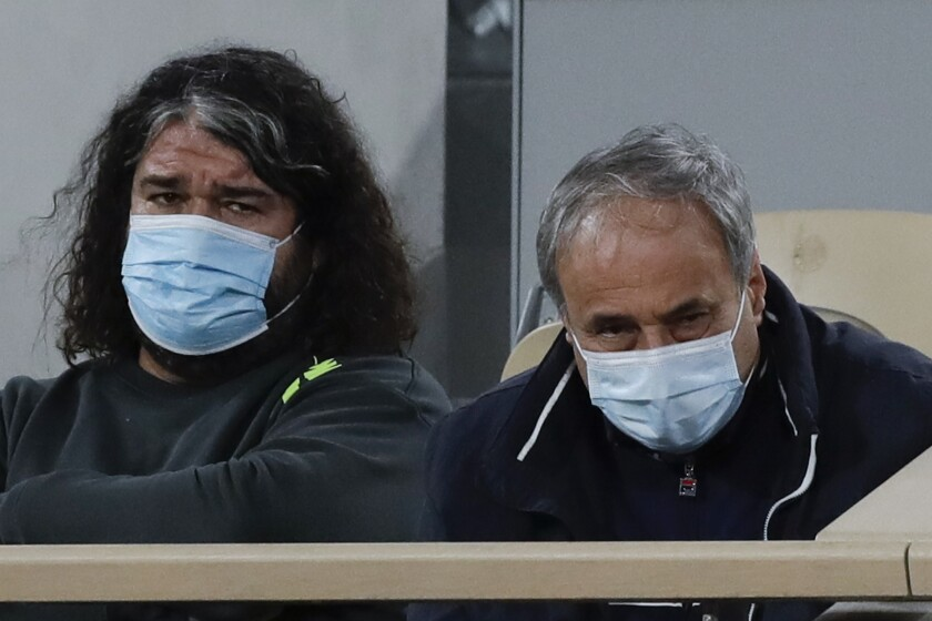 Alexander Kenin, father of Sofia Kenin of the U.S., right, and Emmanuel Planque, coach of France's Fiona Ferro, left, watch the fourth round match of the French Open tennis tournament between Kenin and Ferro at the Roland Garros stadium in Paris, France, Monday, Oct. 5, 2020. (AP Photo/Alessandra Tarantino)