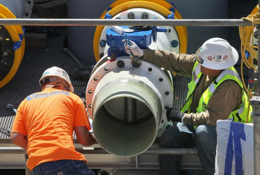 Workers assemble pipes last year at the Carlsbad Desalination Project.