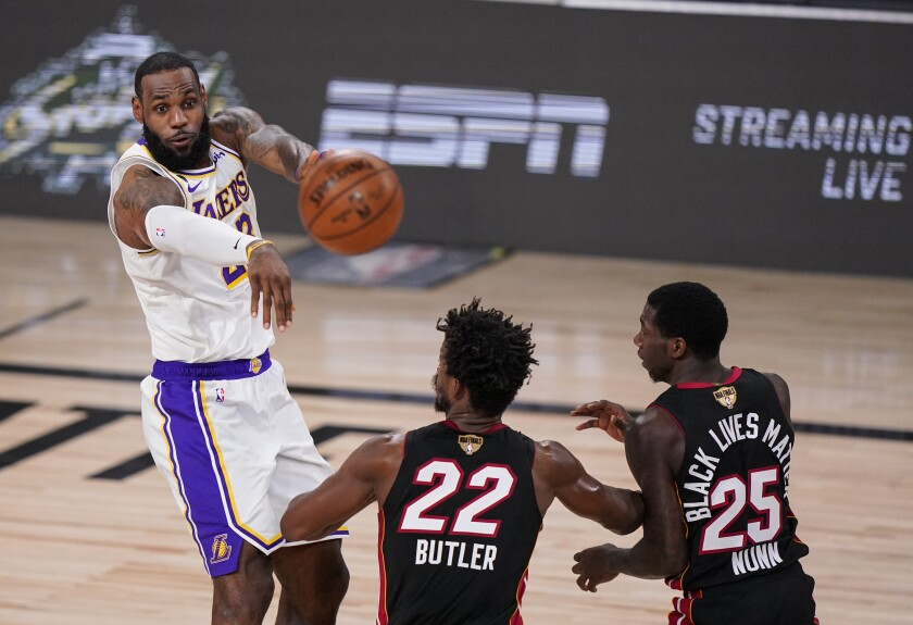 LeBron James passes the ball against Jimmy Butler and Kendrick Nunn during the first half in Game 3.