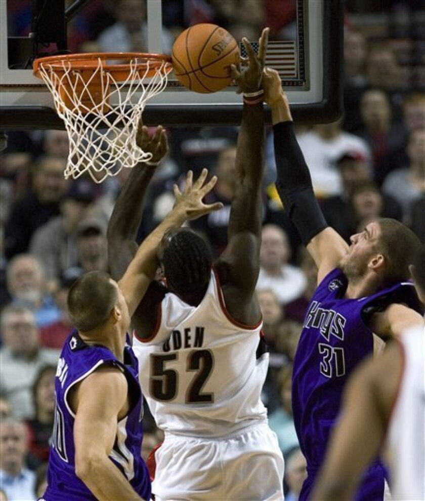 Portland Trail Blazers center Greg Oden, middle, is fouled by Sacramento Kings center Spencer Hawes, right, as Kings forward Jon Brockman defends at left during the first quarter of an NBA preseason basketball game in Portland, Ore., Tuesday, Oct. 6, 2009. (AP Photo/Don Ryan)