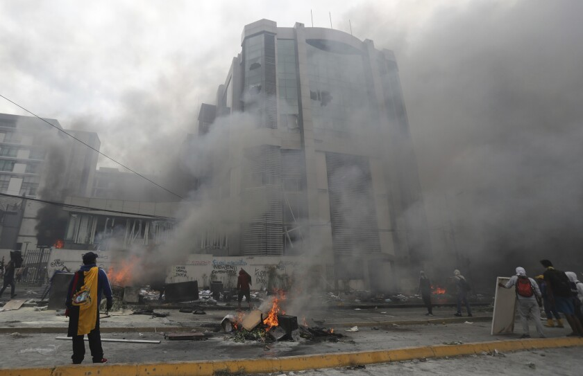 The national auditor's office building burns during clashes between anti-government demonstrators and police in Quito, Ecuador, Saturday, Oct. 12, 2019. President Lenín Moreno ordered the army onto the streets of Ecuador's capital Saturday after a week and a half of protests over fuel prices devolved into violent incidents, with masked protesters attacking a television station, newspaper and the national auditor's office. (AP Photo/Dolores Ochoa)