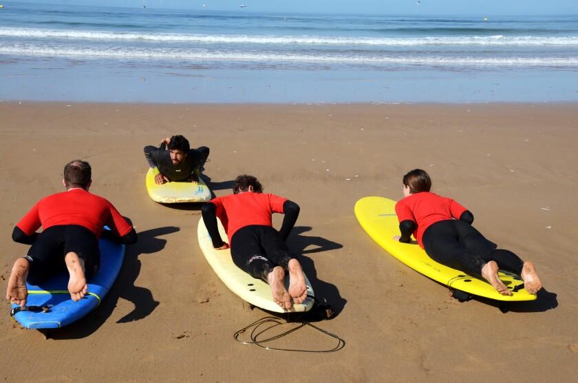 Brahim LeFrere teaches a class of European novice surfers on a beach on Taghazout Bay on Morocco's Atlantic coast.