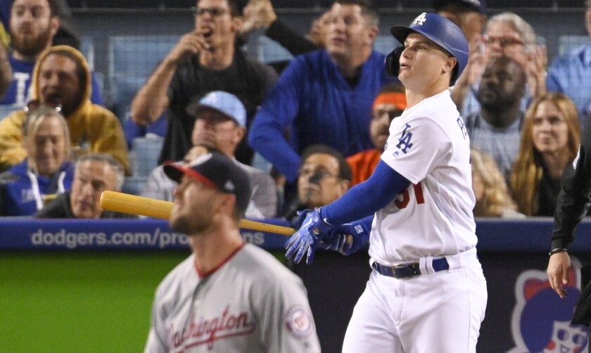 Joc Pederson tracks the ball after hitting a home run. Washington pitcher Hunter Strickland is in the foreground.