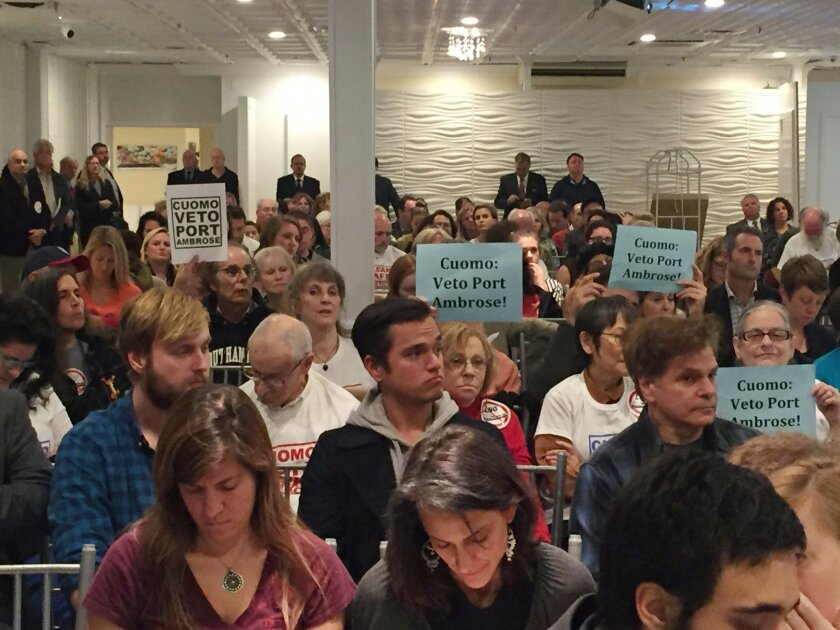 In this Nov. 2, 2015 photo, signs opposing a proposed offshore liquefied natural gas pipeline can be seen in the crowd during a meeting at the Long Beach Hotel in Long Beach, N.Y. Liberty Natural Gas LLC wants to build an offshore gas terminal in the waters between New York and New Jersey that will