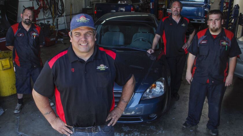 TJ Crossman, center, with his mechanical team at TJ Crossman Auto Repair in Vista. For the fourth year in a row, he will give away a newly rehabbed car to a needy individual in August.