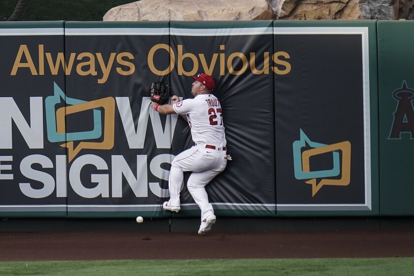 Angels' Mike Trout collides with the wall while trying to catch a triple.