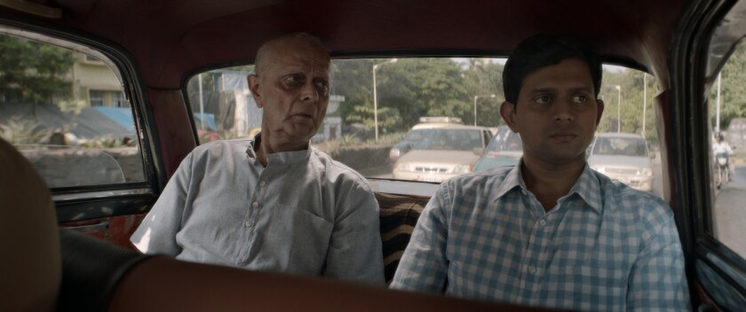 Two men sit in the rear seat of a vehicle.