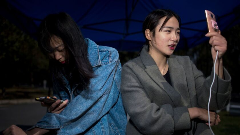 Jiang Mengna, right, broadcasts a live stream to viewers from Yiwu Industrial and Commercial College in Zhejiang province. Millions of Chinese millennials are speaking directly to the country's 700 million smartphone users, streaming their lives to lucrative effect.